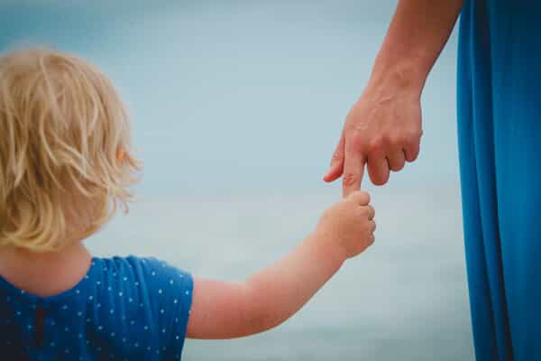 parent with custody holding their child's hand